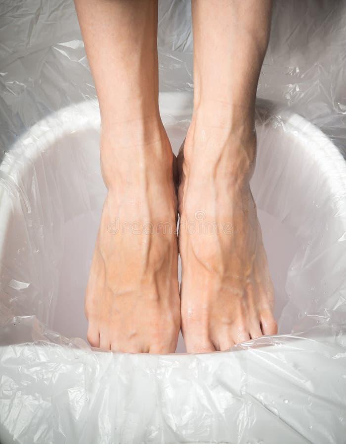 Pieds fatigués, bain de détente de pied Élimination de l'effort des jambes photographie stock libre de droits