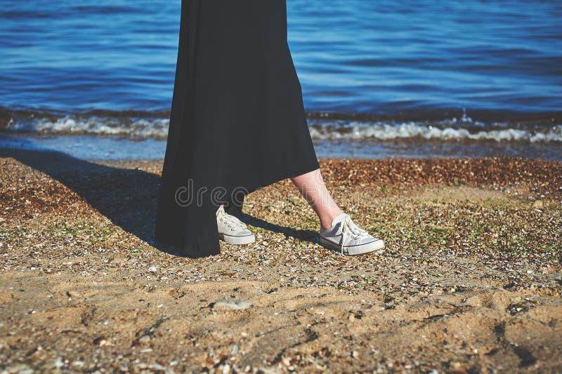 Pieds femelles dans des espadrilles blanches sur le sable Promenade le long de la plage Wom image stock