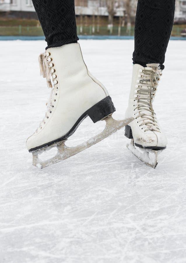 Pieds femelles dans des manies figurées sur la piste de patinage images stock