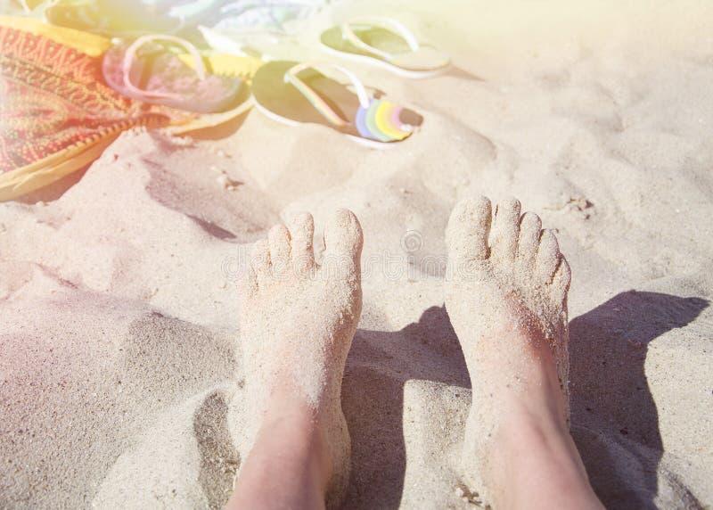 Pieds femelles dans le sable au soleil sur la plage photos stock