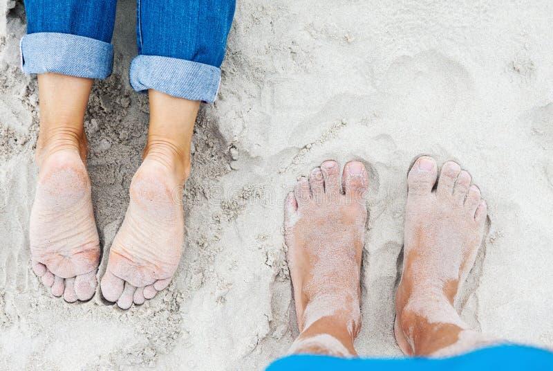 Pieds femelles et masculins de Sandy sur la plage photo libre de droits