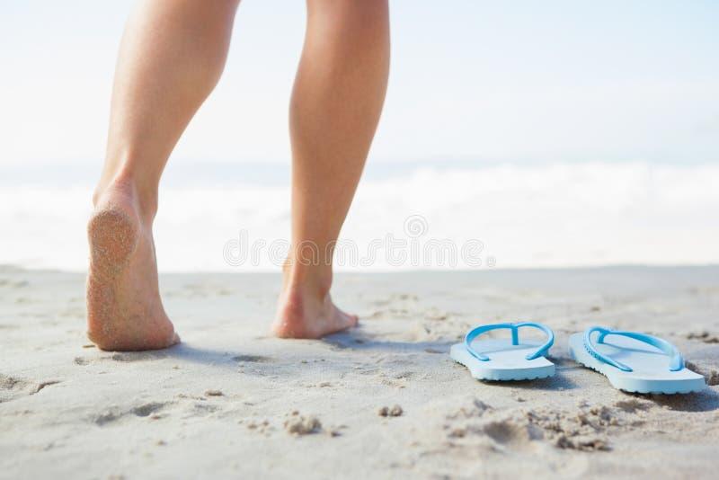 Pieds femelles faisant un pas sur le sable près des bascules électroniques photos stock