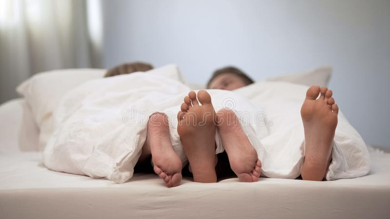 Pieds heureux de couples dans le lit de lune de miel, belle conversation dans le matin, mariage photo libre de droits