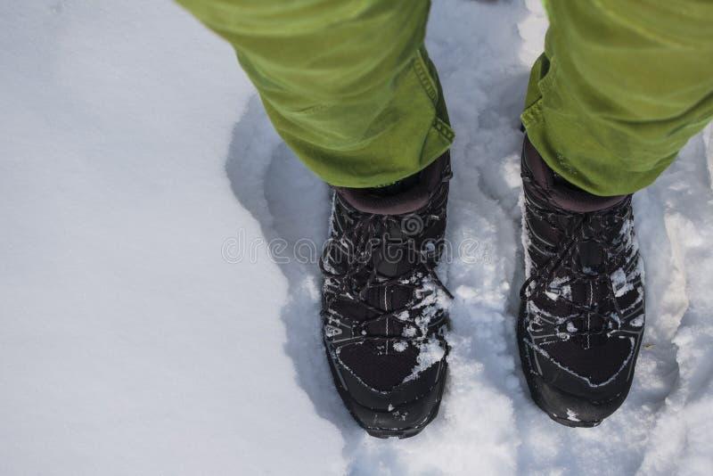 Pieds humains en augmentant des bottes dans la neige photos libres de droits
