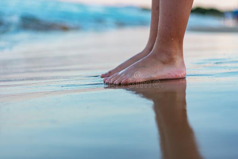 Pieds nus à une plage au coucher du soleil images libres de droits