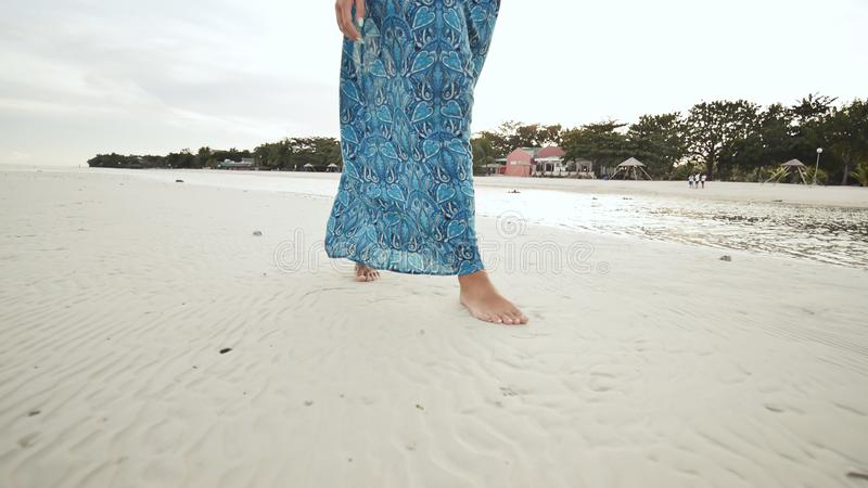 Pieds nus dans une longue robe bleue La fille marche nu-pieds sur la plage sablonneuse blanche de la côte philippine exotique photos libres de droits