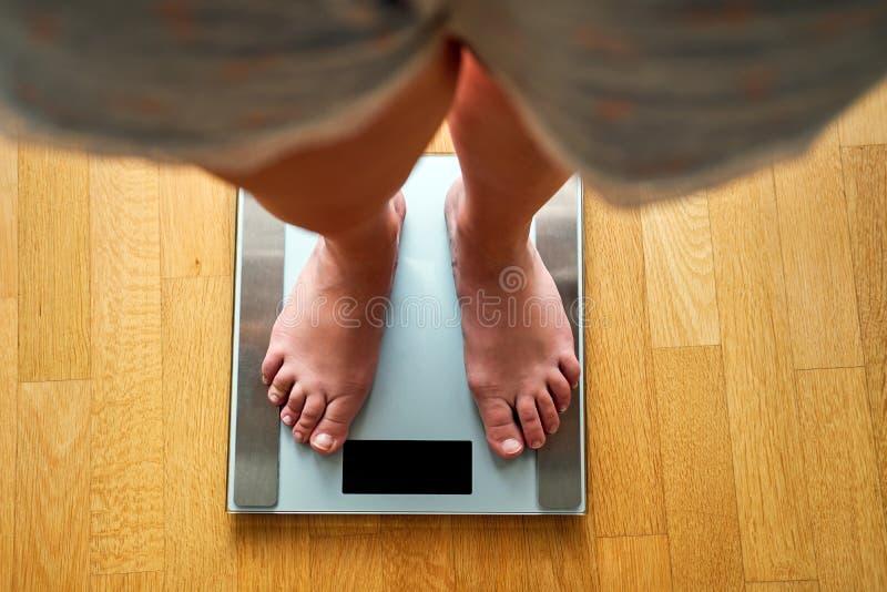 Pieds nus femelles avec l'échelle de poids photographie stock