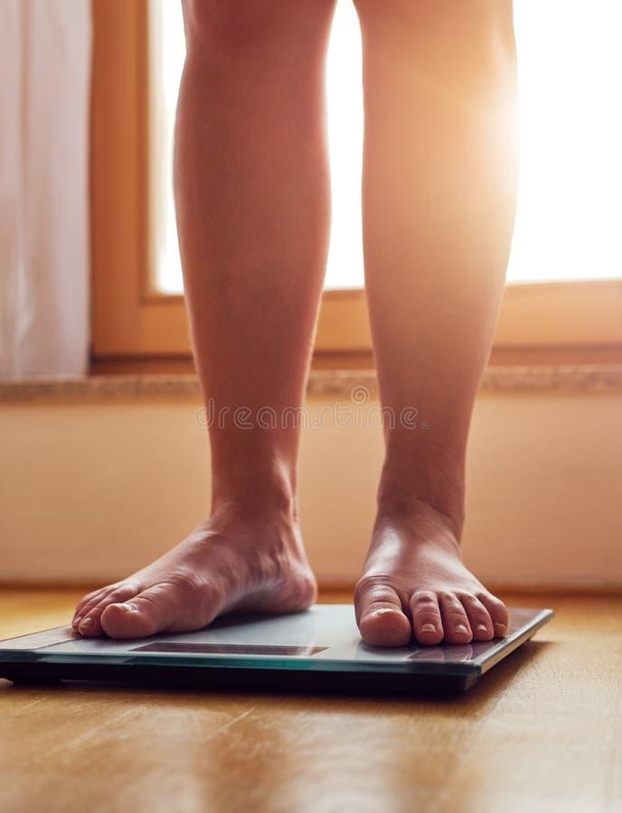 Pieds nus femelles sur l'échelle de poids photographie stock libre de droits
