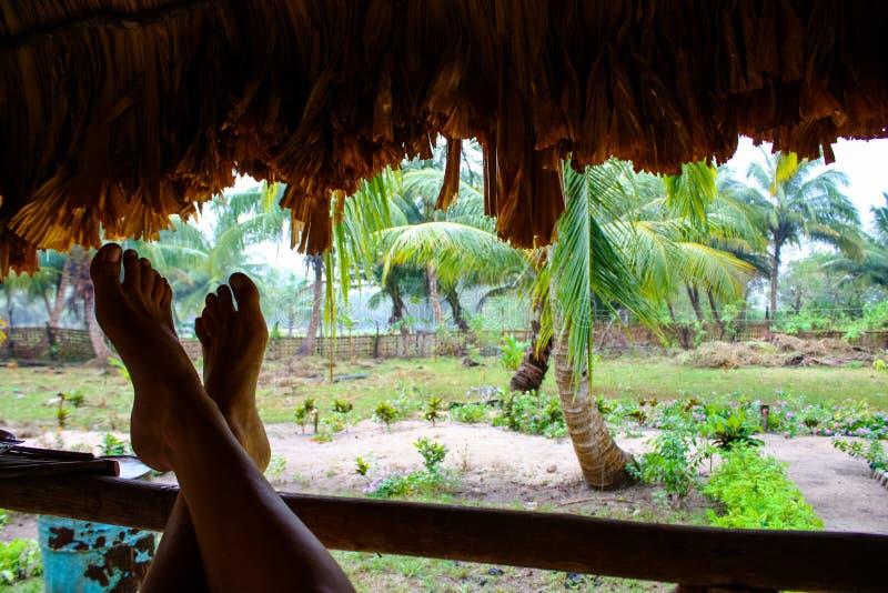 Pieds se penchant contre une barrière dans une hutte de jungle photographie stock libre de droits