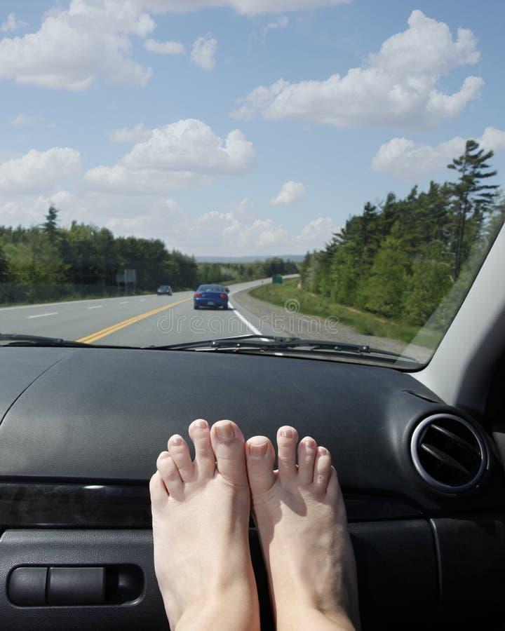 Pieds sur le tableau de bord sur des vacances ou le voyage par la route image libre de droits