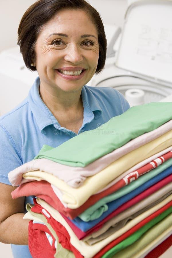 piegato tenendo la donna della lavanderia immagini stock