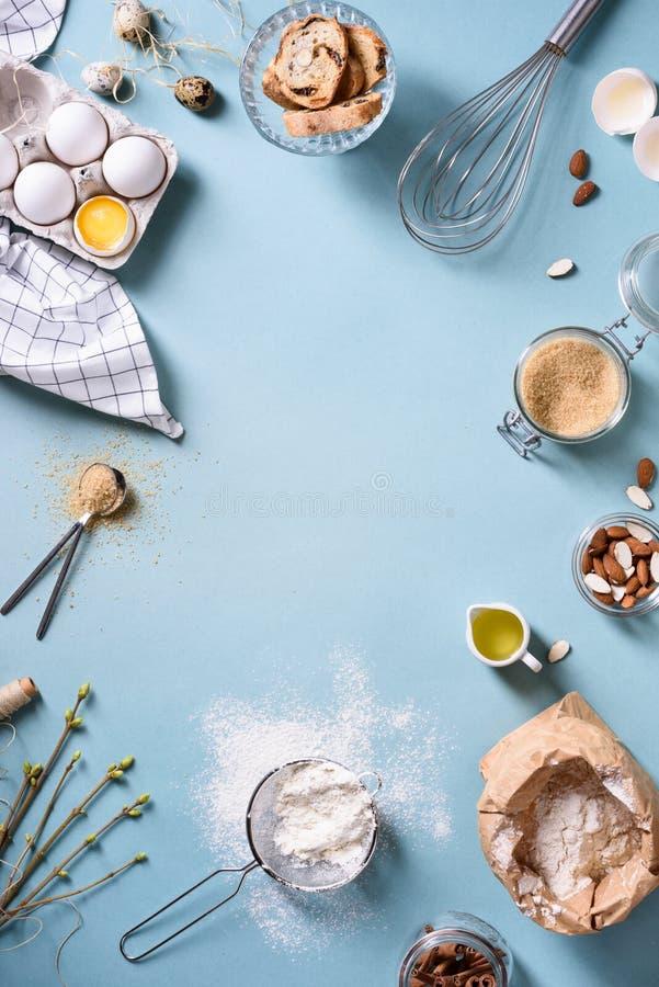 Piekarni tła rama Świezi kulinarni składniki - jajko, mąka, cukier, masło, dokrętki nad błękitnym tłem Wiosna kulinarny temat zdjęcia stock