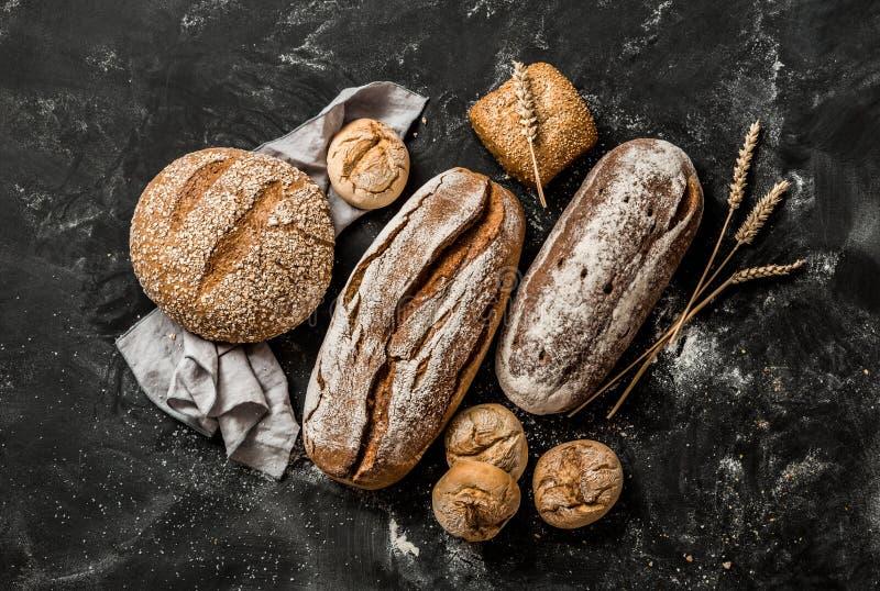 Piekarnia - nieociosani skorupiaści bochenki chleb i babeczki na czerni obraz royalty free