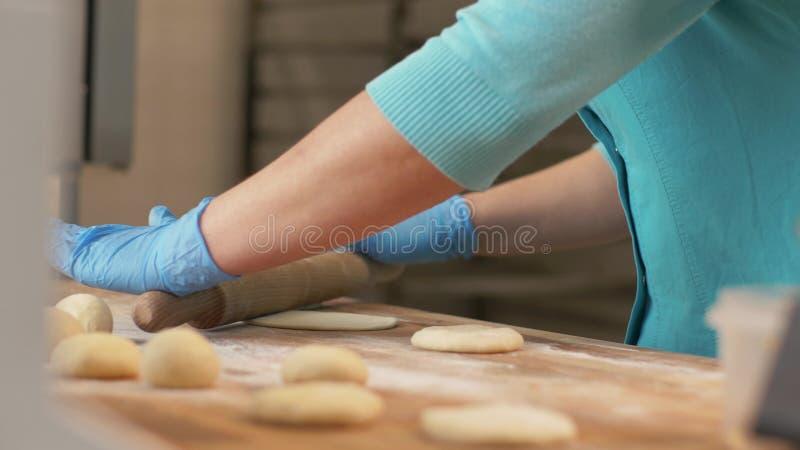 Piekarnianej ręki toczny ciasto przed wypiekowymi ciastami na stole w bakehouse zakończeniu up obraz stock
