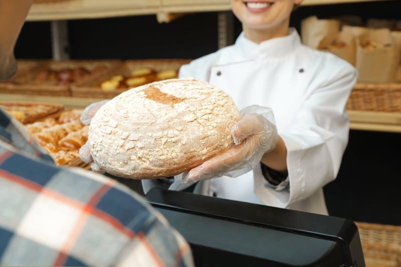 Piekarniany daje klient świeży chleb w sklepie zdjęcia stock