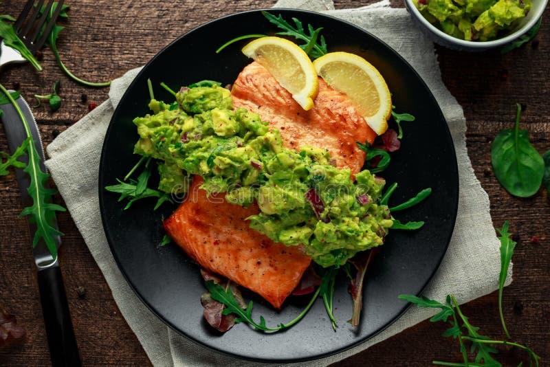 Piekarnik gotujący łososiowy stek, przepasuje z avocado salsa i zielenieje na czarnym talerzu tabela drewna zdrowa żywność obrazy stock