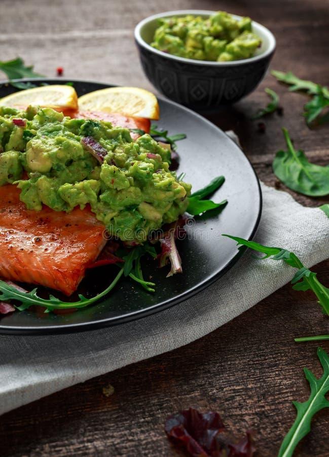 Piekarnik gotujący łososiowy stek, przepasuje z avocado salsa i zielenieje na czarnym talerzu tabela drewna zdrowa żywność obrazy royalty free