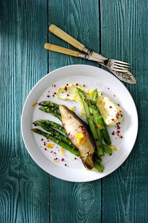 Piekarnik piec denny rybi polędwicowego z szparagowym i zielarski masło słuzyć z serem pureed gruli zdjęcia stock