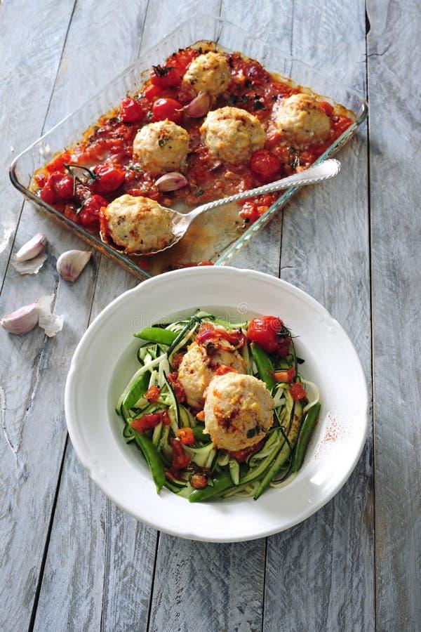Piekarnik piec mięsne piłki z pomidorowym kumberlandem słuzyć z świeżą zucchini sałatką zdjęcia stock