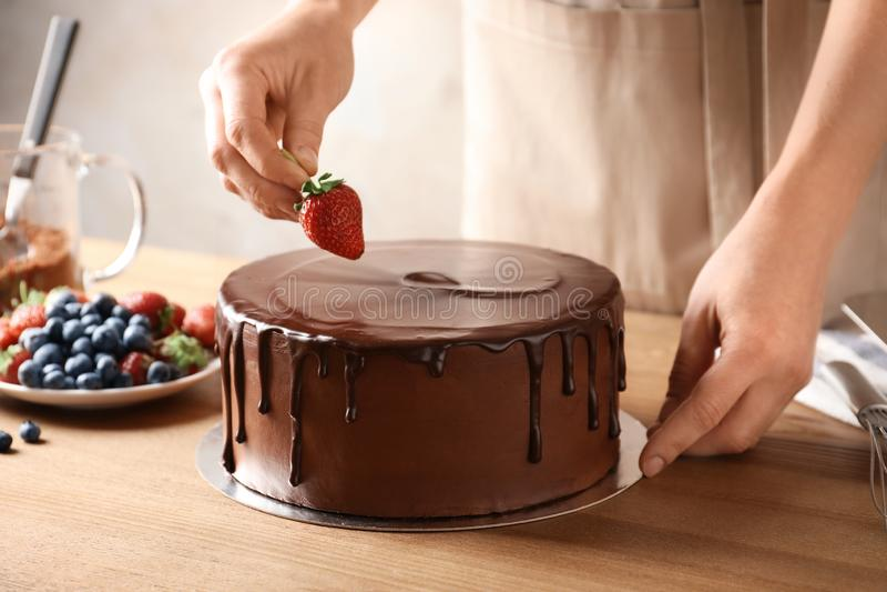Piekarz dekoruje świeżą wyśmienicie domowej roboty czekoladę zdjęcia royalty free