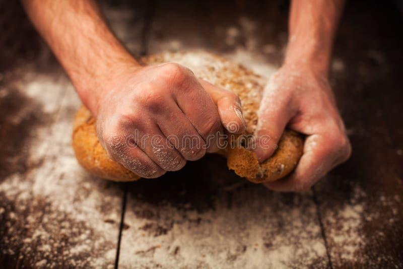 Piekarz ręki z świeżym chlebem na stole fotografia stock
