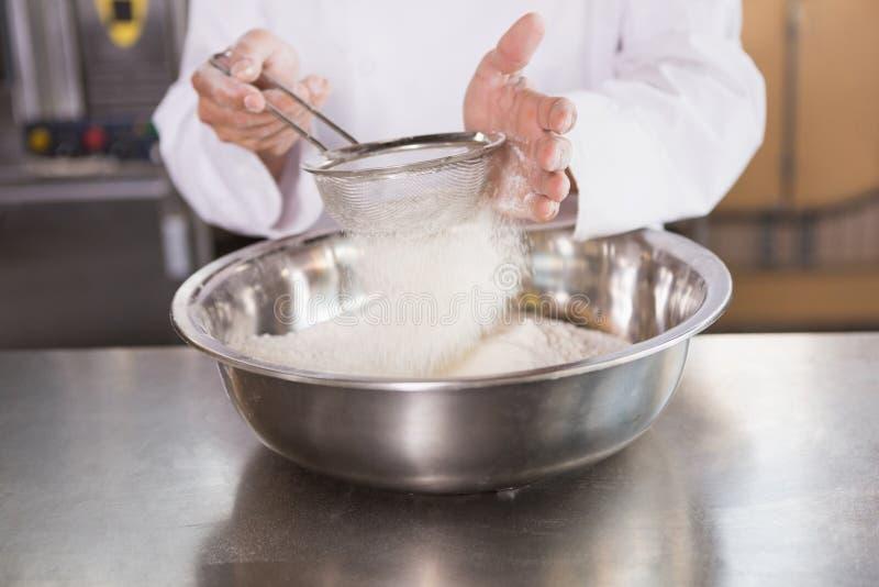 Piekarz sieving mąkę w puchar obrazy royalty free
