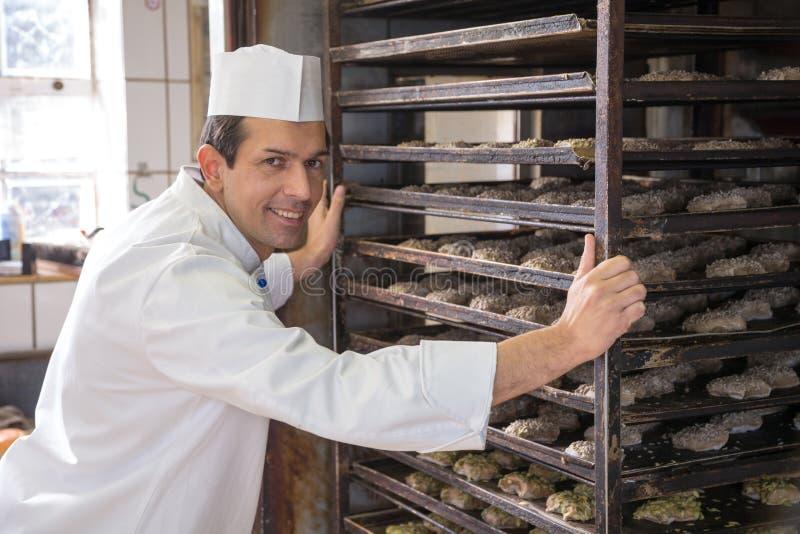 Piekarz stawia stojaka chleb w piekarnika zdjęcia stock