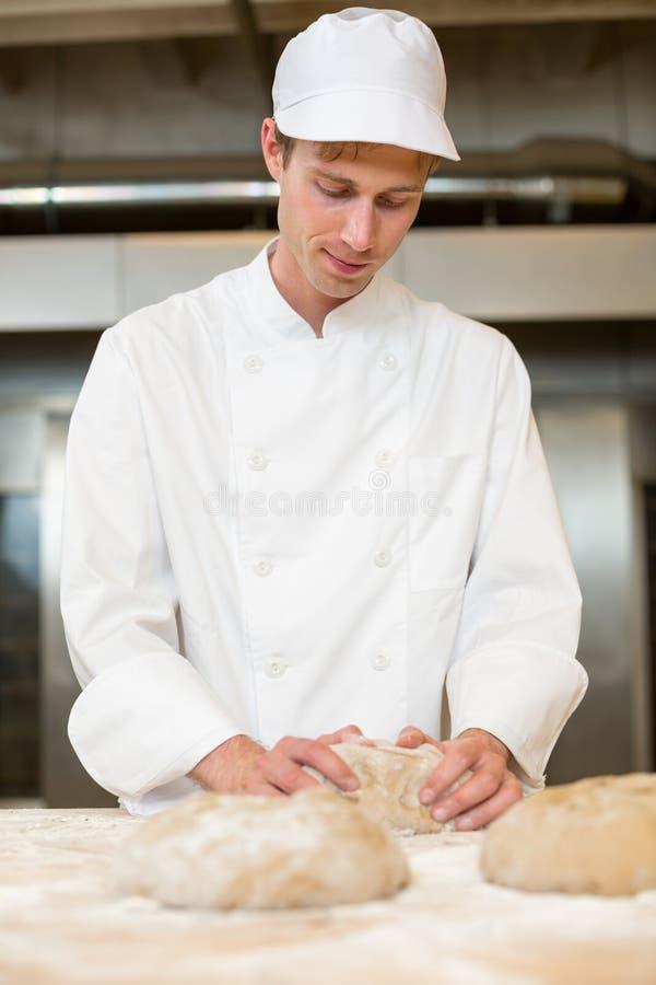 Piekarz ugniata ciasto w piekarni lub bakehouse zdjęcia stock