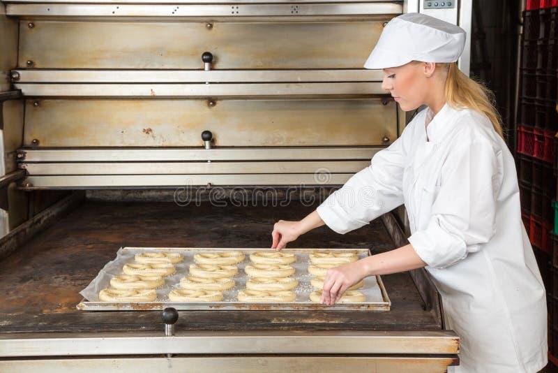 Piekarz w piekarni z pieczenie talerzem pełno precle zdjęcia stock