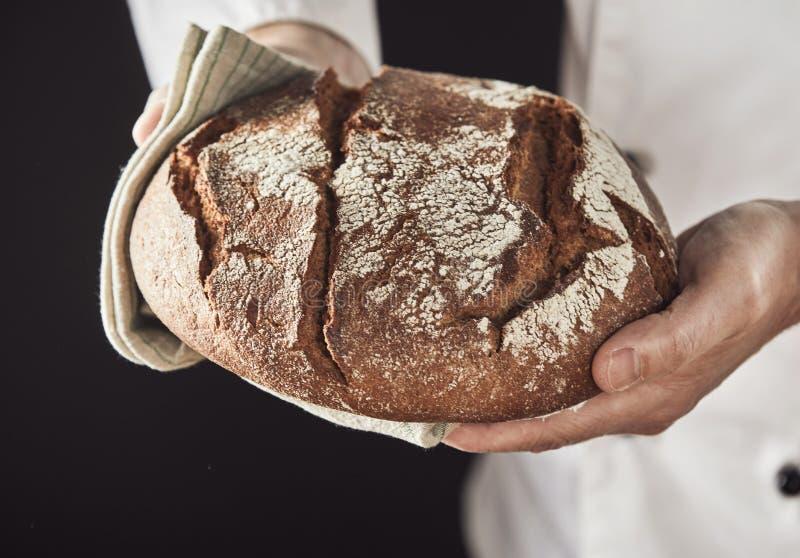 Piekarz wręcza trzymać świeżego bochenek żyto chleb zdjęcie royalty free