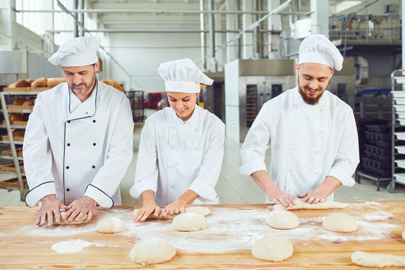 Piekarzi ugniata ciasto w piekarni obraz stock
