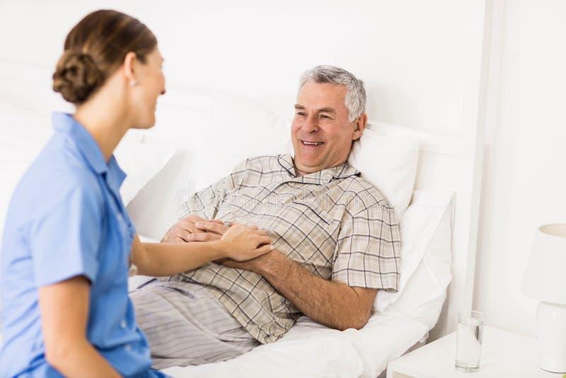 Pielęgniarka bierze opiekę cierpienie seniora pacjent zdjęcia stock