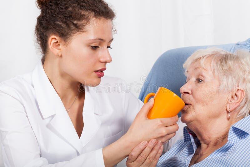 Pielęgniarka daje pić starej kobiety zdjęcie royalty free