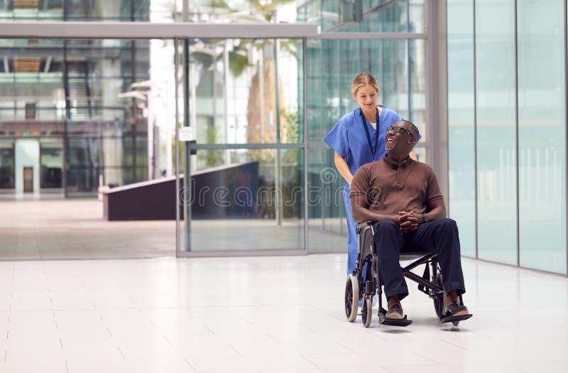 Pielęgniarka Nosiła Kruki Na Wózku Przez Lobby Nowoczesnego Budynku Szpitalnego zdjęcia royalty free