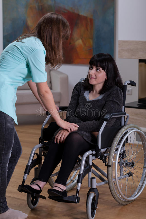 Pielęgniarka opowiada z niepełnosprawną kobietą zdjęcie royalty free