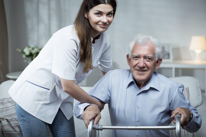 Pielęgniarka pomaga niepełnosprawnego starszego mężczyzna fotografia royalty free