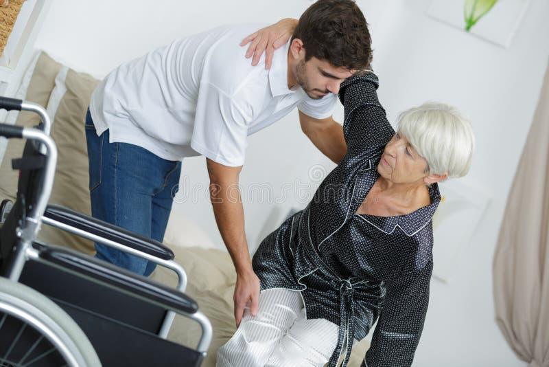 Pielęgniarka pomaga niepełnosprawnemu damy obsiadaniu na wózku inwalidzkim zdjęcia royalty free