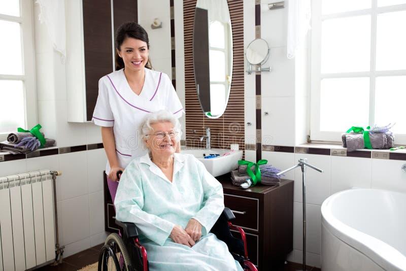 Pielęgniarka pomaga stara kobieta w wózku inwalidzkim obraz royalty free