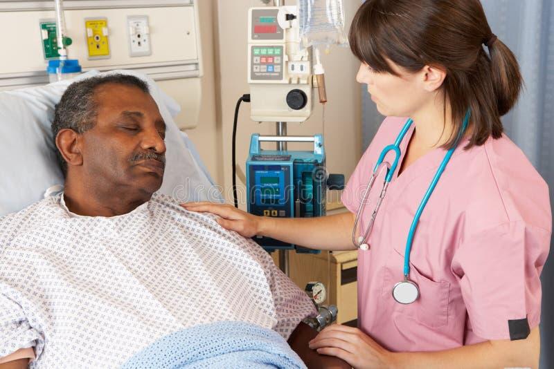 Pielęgniarka Sprawdza Starszego pacjenta Na oddziale fotografia royalty free