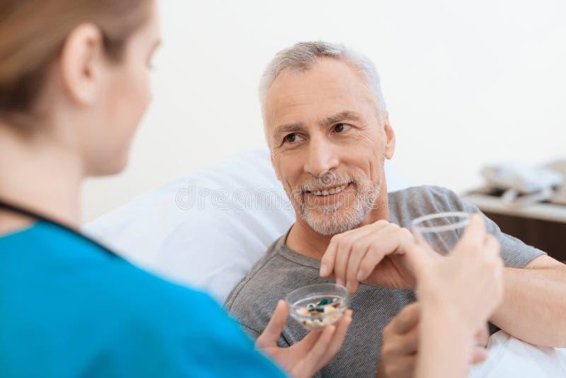 Pielęgniarka stojaki obok starego człowieka i dają on wodnemu i pigułkom Są uśmiechnięci zdjęcie stock