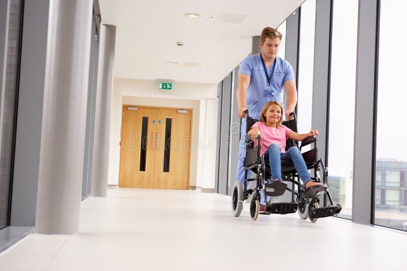 Pielęgniarki dosunięcia dziewczyna W wózku inwalidzkim Wzdłuż korytarza fotografia stock