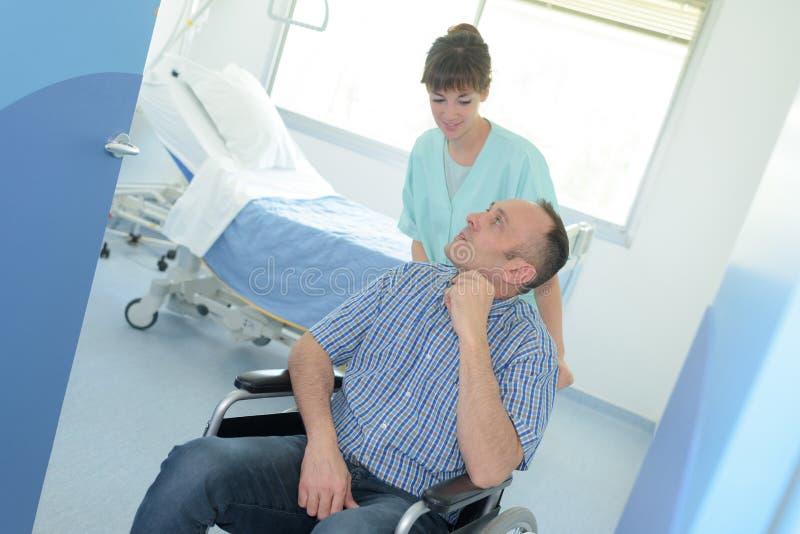 Pielęgniarki dosunięcia niepełnosprawny pacjent przy szpitalem obrazy royalty free