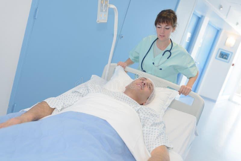 Pielęgniarki dosunięcia pacjent w łóżku obraz royalty free