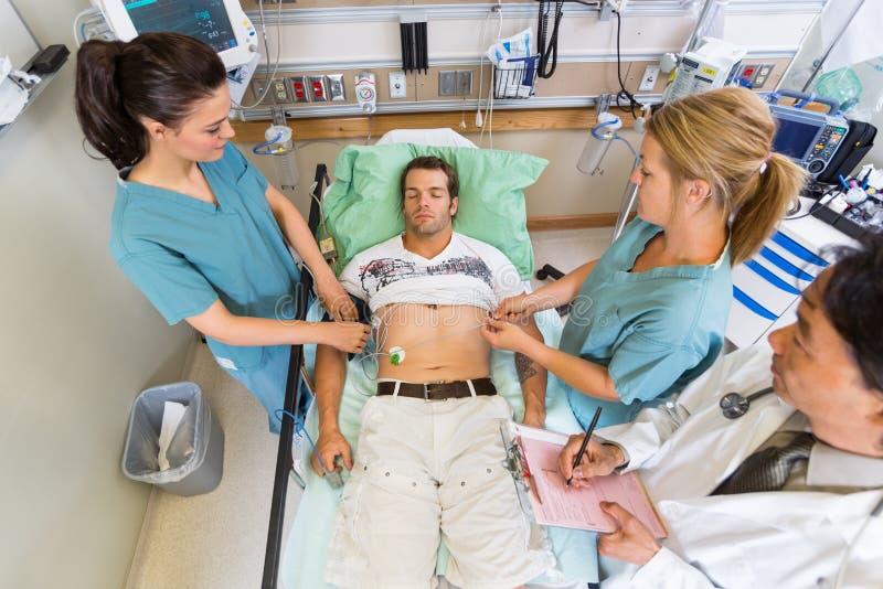 Pielęgniarki I lekarka Egzamininuje pacjenta puls Wewnątrz zdjęcia royalty free