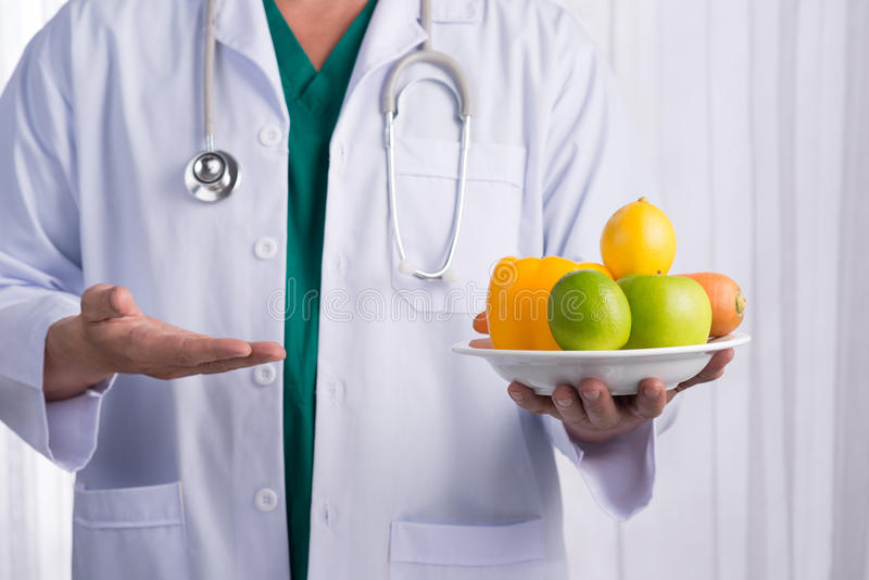 Pielęgniarki lub samiec lekarka daje owoc Opieki zdrowotnej pojęcie odizolowywający zdjęcie stock
