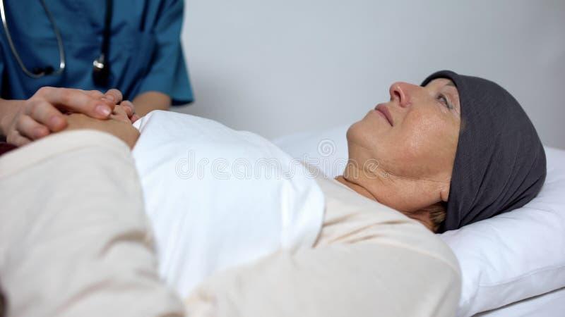Pielęgniarki mienia ręka pacjent z nowotworem, dziękczynny żeński patrzeje hospicjumu pracownik zdjęcia royalty free