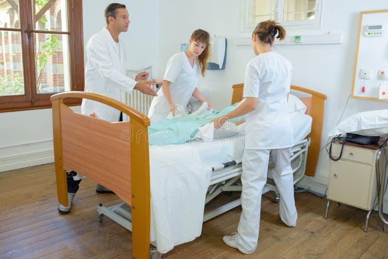 Pielęgniarki podnosi pacjenta pod doktorskim ` s nadzorem zdjęcia stock