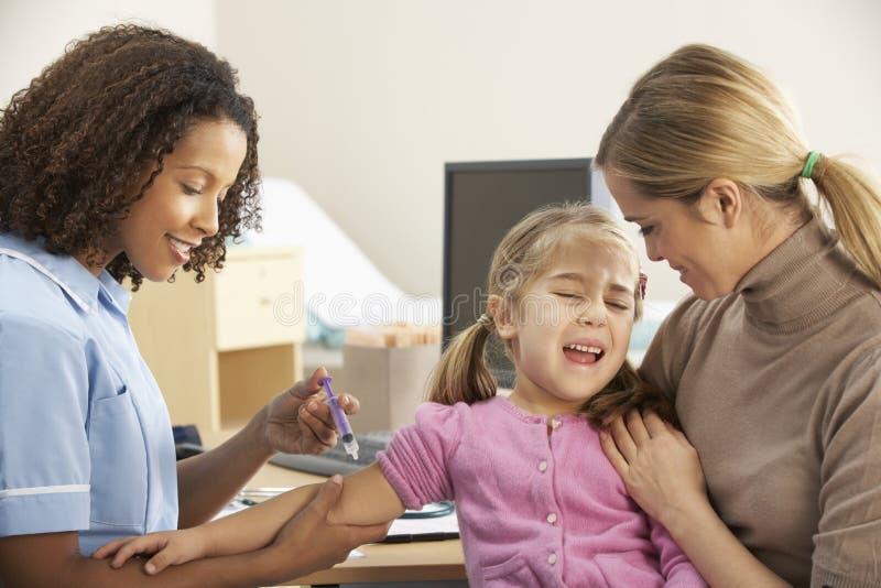 Pielęgniarki wstrzykiwania dziecko z matką fotografia stock