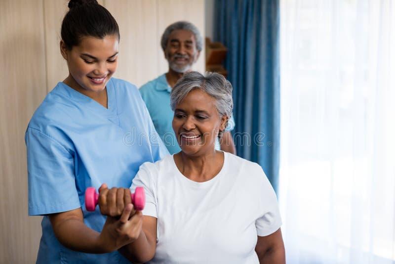 Pielęgniarki wytyczna starsza kobieta w podnośnym dumbbell obrazy royalty free