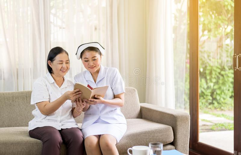 Pielęgnuje brać opiekę czyta książkę jej cierpliwa dojrzała azjatykcia starsza kobieta, Starszy zdrowy pojęcie zdjęcie royalty free